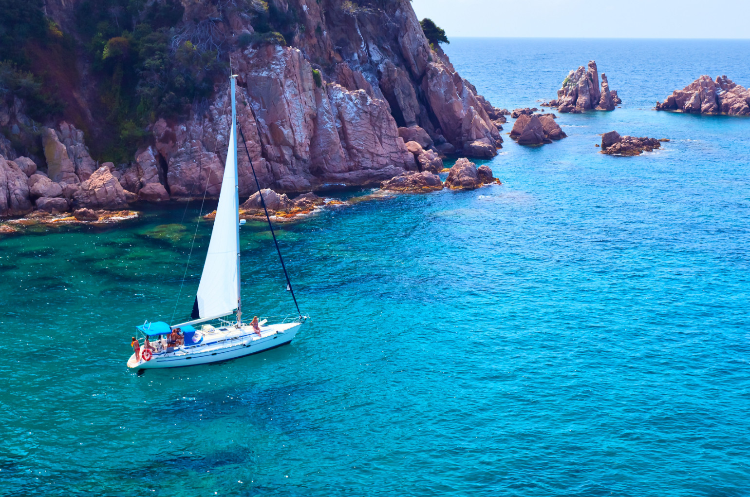 Yacht in sea by coastline